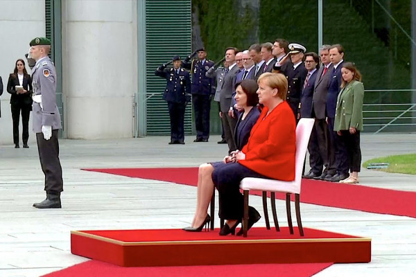 Merkel himni yenə oturaraq dinlədi